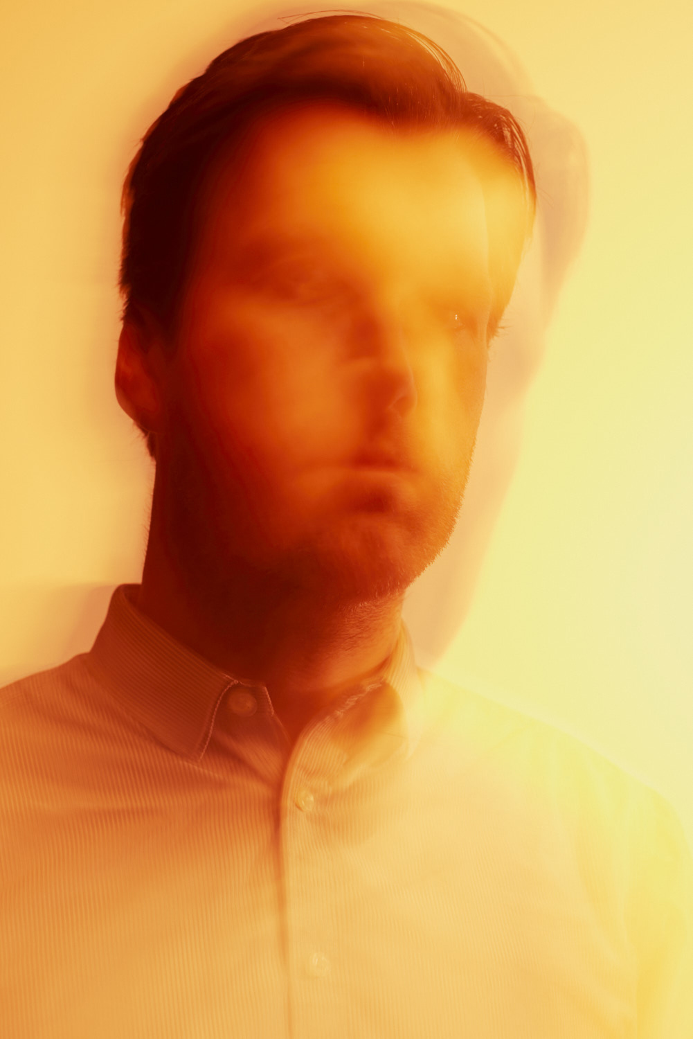 Abstract portrait of a man in yellow gloomy light.